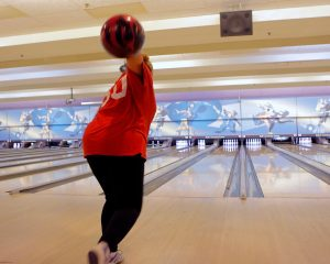 Woman about to release bowling ball down an alley at Rab's Country Lanes