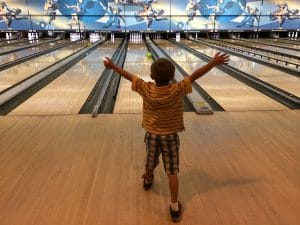 Child with hands in air after releasing their bowling ball down an alley at Rab's Country Lanes