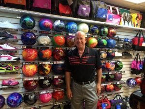 Smiling man standing in front of wall of bowling balls