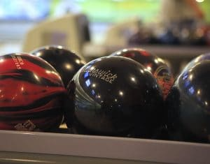 Close up photo of bowling balls in ball return